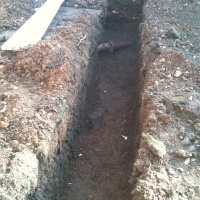 Foundation trench excavated with care and clay storm drain left intack
